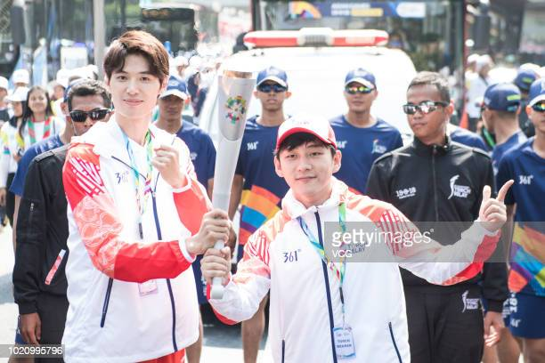 Chinese fencer Sun Wei and Chinese host Du Haitao carry the torch during the last torch relay ahead of the opening ceremony of the 2018 Asian Games...