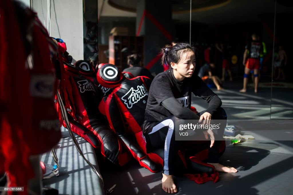 Chinese fighter Lin Heqin rests in front of a mirror at Guangdong