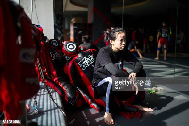 Chinese fighter Lin Heqin rests in front of a mirror at Guangdong Olympic Centre Stadium on November 29 2017 in Guangzhou Guangdong Province of China...