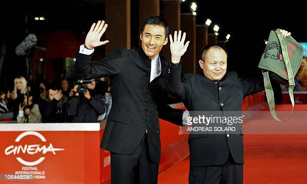 Chinese film director Liu Bingjian flanked by Chinese actor Hu Bing waves on the red carpet before the screening of their latest movie The Back at...