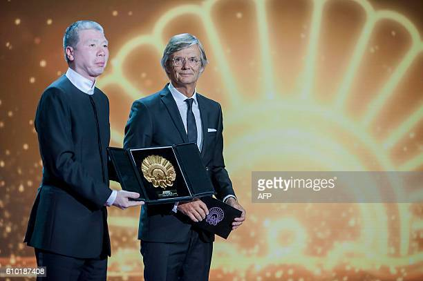 """Chinese film director Xiaogang Feng holds his """"Concha de Oro"""" award to the best film, beside jury president Danish film director Bille August, for..."""