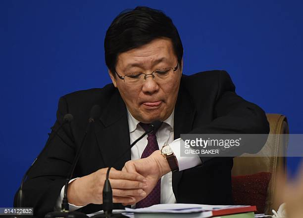 Chinese Finance Minister Lou Jiwei checks his watch during a National People's Congress press conference in Beijing on March 7 2016 China's labour...
