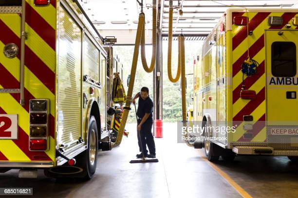 chinese fireman sweeping floor near fire trucks - fire station - fotografias e filmes do acervo