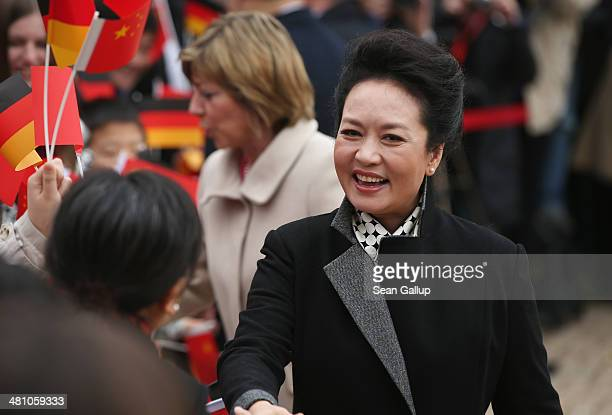 Chinese First Lady Peng Liyuan and German First Lady Daniela Schadt greet students at Schloss Bellevue on March 28 2014 in Berlin Germany Chinese...