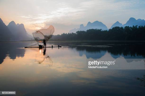 Chinese fisherman fishing with a throw net on river Li near Guilin