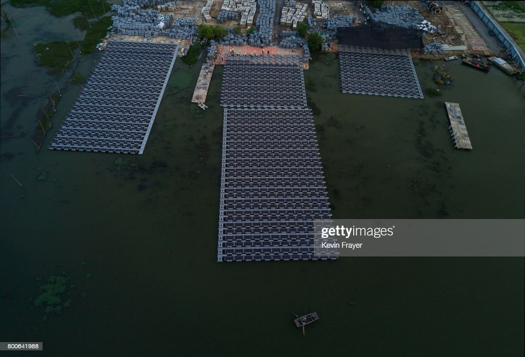 A Chinese fisherman paddles passed workers building a large floating solar farm project under construction by the Sungrow Power Supply Company on a lake caused by a collapsed and flooded coal mine on June 13, 2017 in Huainan, Anhui province, China. The floating solar field, billed as the largest in the world, is built on a part of the collapsed Panji No.1 coal mine that flooded over a decade ago due to over-mining, a common occurence in deep-well mining in China's coal heartland. When finished, the solar farm will be made up of more than 166,000 solar panels which convert sunlight to energy, and the site could potentially produce enough energy to power a city in Anhui province, regarded as one of the country's coal centers. Local officials say they are planning more projects like it, marking a significant shift in an area where long-term intensive coal mining has led to large areas of subsidence and environmental degradation. However, the energy transition has its challenges, primarily competitive pressure from the deeply-established coal industry that has at times led to delays in connecting solar projects to the state grid. Chinaâs government says it will spend over US $360 billion on clean energy projects by 2020 to help shift the country away from a dependence on fossil fuels, and earlier this year, Beijing canceled plans to build more than 100 coal-fired plants in a bid to ease overcapacity and limit carbon emissions. Already, China is the leading producer of solar energy, but it also remains the planetâs top emitter of greenhouse gases and accounts for about half of the worldâs total coal consumption.