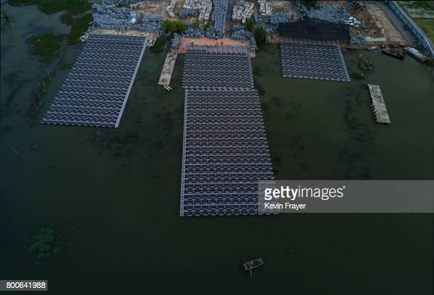 Chinese fisherman paddles passed workers building a large floating solar farm project under construction by the Sungrow Power Supply Company on a...