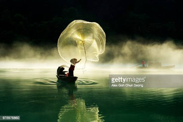 Chinese fisherman throwing net on lake, Zhengzhou, Hunan, China