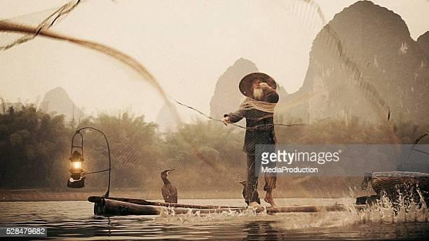 Chinese fisherman throwing net on river Li