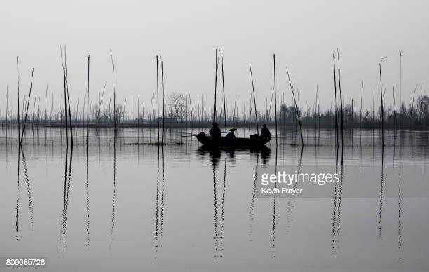 Chinese fishermen ride in a boat on land was flooded out more than a decade ago near the site of a large floating solar farm project under...