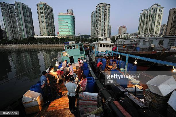 Chinese fishermen sell their day's catch to customers at a fishing port in Zhuhai southern China's Guangdong province on September 20 2010 China's...