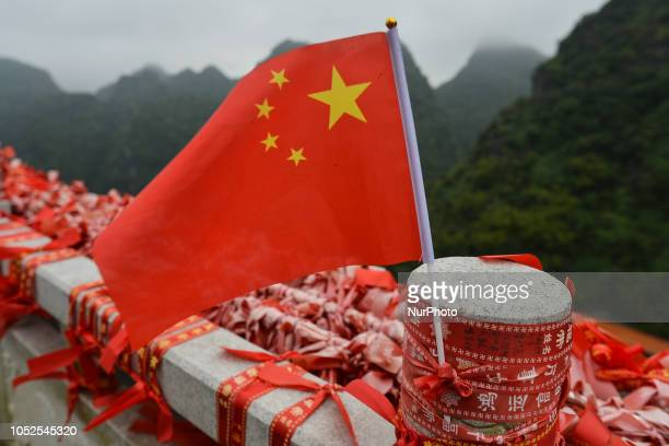A Chinese flag and rubans with prayers left in the Putuo Temple near the final point of the fourth stage 1522km from Nanning to Nongla Scenic Area of...