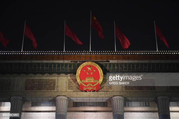 A Chinese flag flies above the national emblem on the Great Hall of the People after a plenary session of the National People's Congress in Beijing...