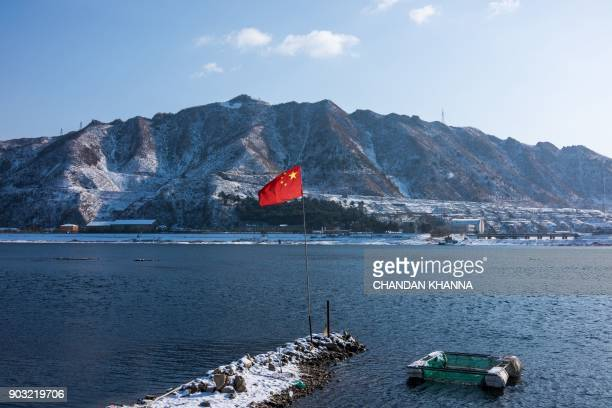 Chinese flag flies by the Yalu river while North Korea's Sakchu county in North Pyongan province is seen from the Chinese border city of Dandong on...