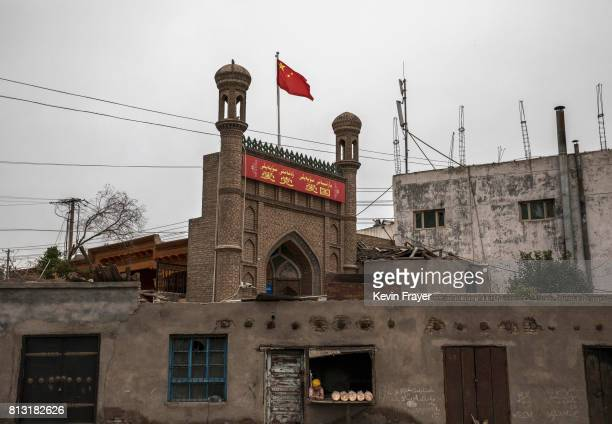 Chinese flag flies over a local mosque recently closed by authorities as an ethnic Uyghur woman sells bread at her bakery on June 28 2017 in the old...