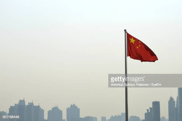 chinese flag in city against clear sky - chinese flag stock pictures, royalty-free photos & images
