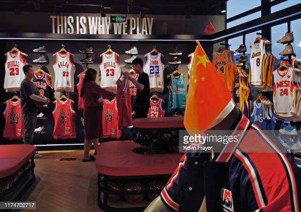 A Chinese flag is seen placed on a mannequin wearing the USA basketball uniform as Chinese shoppers look at clothing in the NBA flagship retail store...