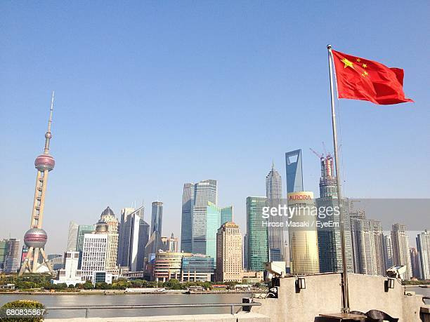 Chinese Flag Waving Against Oriental Pearl Tower And Modern Buildings In City