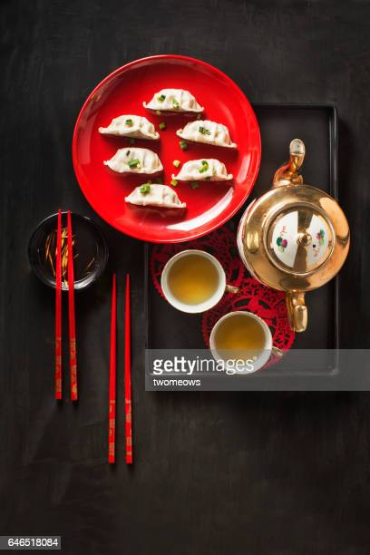 Chinese food dumpling and tea set on black rustic table top.