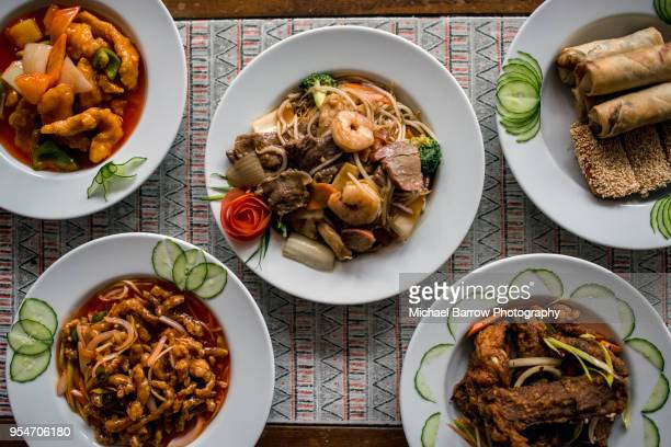 chinese food on plates in restaurant - chinese food stock pictures, royalty-free photos & images