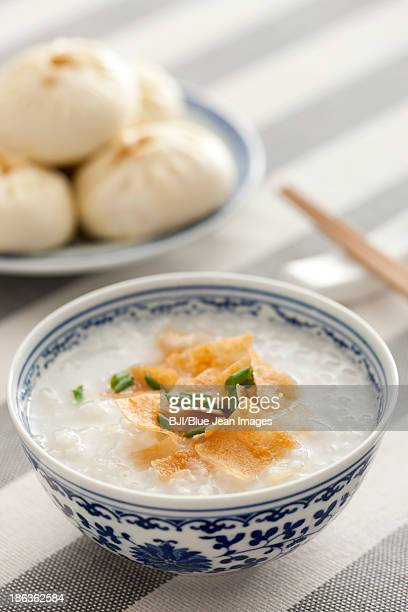 chinese food rice porridge and steamed buns - congee stock photos and pictures
