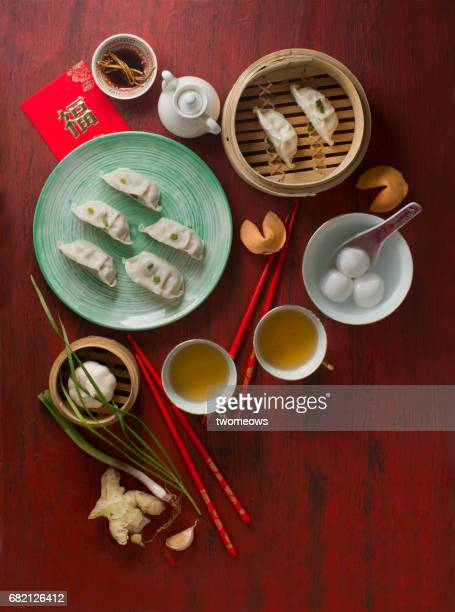 Chinese food steamed dumpling and tea served on red rustic background.
