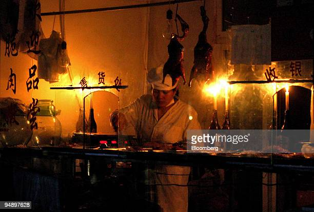 Chinese food store clerk works under candle light in a blacked out portion of Shanghai China on August 16 2004