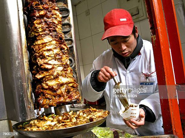A Chinese food vendor prepares roast meats at the Wangfujing commercial shopping street in Beijing 15 January 2008 China's quality watchdog on 14...
