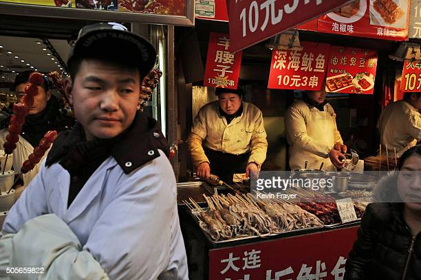 Chinese food vendors wait for customers at a market on January 19 2016 in Beijing China In 2015 China's economy grew at its slowest rate in a quarter...
