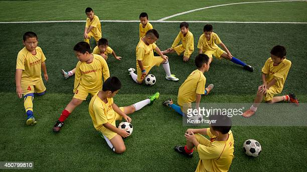 Chinese football players stretch before training at the Evergrande International Football School on June 12 2014 near Qingyuan in Guangdong Province...