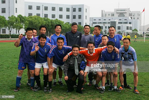 Chinese football star Fan Zhiyi poses for a picture with inmates and warden at Qingpu Prison on May 18 2005 in Shanghai China Fan visited the prison...