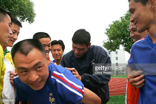 Chinese football star Fan Zhiyi signs his name on the clothes of an inmate at Qingpu Prison on May 18 2005 in Shanghai China Fan visited the prison...