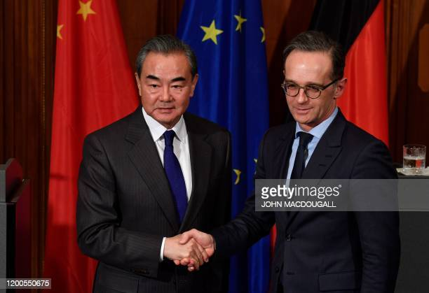 Chinese Foreign Minister Wang Yi and German Foreign Minister Heiko Maas shake hands after a joint press conference after talks on February 13, 2020...