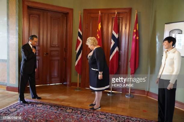Chinese Foreign Minister Wang Yi greets Norway's Prime Minister Erna Solberg and Norway's Foreign Minister Ine Eriksen Soreide during a visit to...