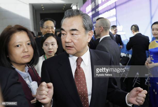 Chinese Foreign Minister Wang Yi is surrounded by reporters before attending an event in Beijing on April 11 2017 Chinese officials warned against...