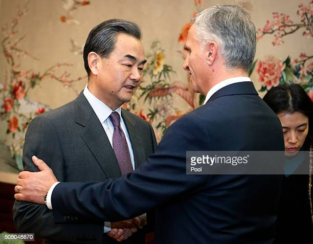 Chinese Foreign Minister Wang Yi left and Swiss Foreign Minister Didier Burkhalter right shake hands before a bilateral meeting at the Ministry of...