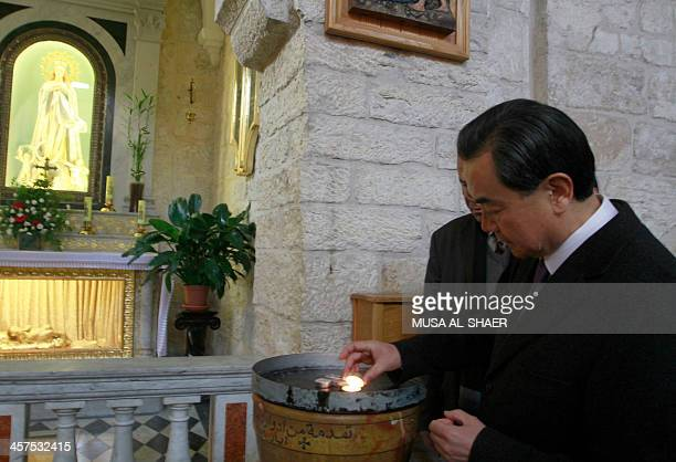 Chinese Foreign Minister Wang Yi lights a candle during his visit to the Church of Nativity revered as the site of Jesus Christ's birth in the West...