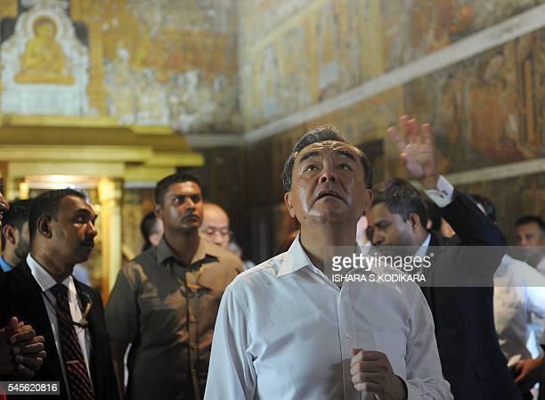 Chinese Foreign Minister Wang Yi looks on during a visit to the Kelaniya Rajamaha temple in Kelaniya on July 9 2016 Wang Yi is in Sri Lanka for a...