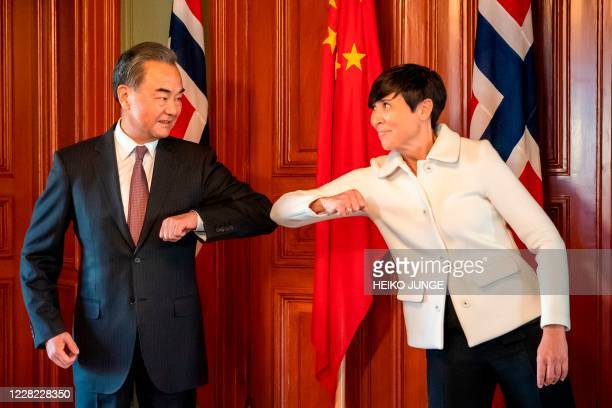 Chinese Foreign Minister Wang Yi makes an elbow bump with Norway's Foreign Minister Ine Eriksen Soreide during a visit to Norway on August 27, 2020...