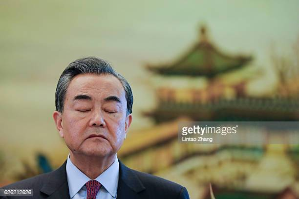 Chinese Foreign Minister Wang Yi reacts during a joint press conference with United Nations Secretary Generaldesignate Antonio Guterres after a joint...