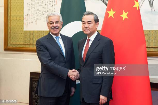 Chinese Foreign Minister Wang Yi shakes hands with Pakistan's Foreign Minister Khawaja Muhammad Asif at Diaoyutai State Guesthouse in Beijing on...