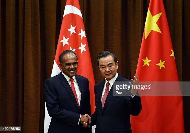 Chinese Foreign Minister Wang Yi shakes hands with Singapore's Foreign Minister K Shanmugam on June 12 2014 in Beijing China