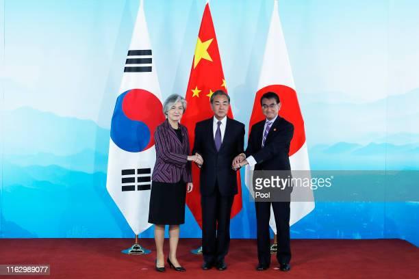 Chinese Foreign Minister Wang Yi South Korean Foreign Minister Kang Kyungwha and Japanese Foreign Minister Taro Kono shake hands ahead the ninth...