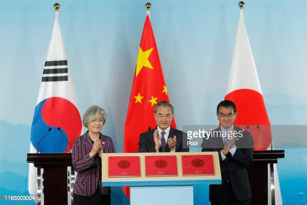 Chinese Foreign Minister Wang Yi South Korean Foreign Minister Kang Kyungwha and Japanese Foreign Minister Taro Kono clap during a ceremony to launch...