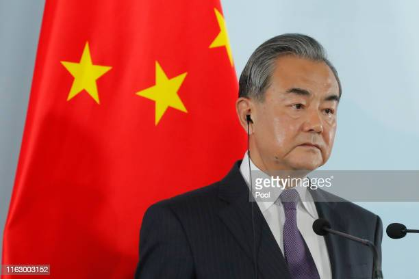 Chinese Foreign Minister Wang Yi speaks beside South Korean Foreign Minister Kang Kyungwha and Japanese Foreign Minister Taro Kono during a press...