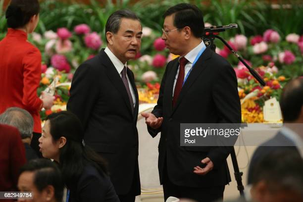 Chinese Foreign Minister Wang Yi speaks with a member of staff ahead of a welcome banquet for the Belt and Road Forum at the Great Hall of the People...