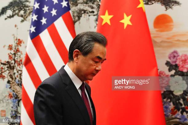 Chinese Foreign Minister Wang Yi walks by US and Chinese national flag as he prepares to meet Secretary of State Rex Tillerson at the Great Hall of...