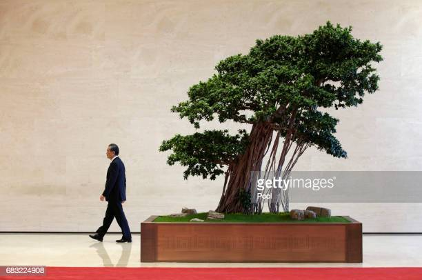 Chinese Foreign Minister Wang Yi walks outside the venue for a news conference by Chinese President Xi Jinping to conclude the Belt and Road Forum...