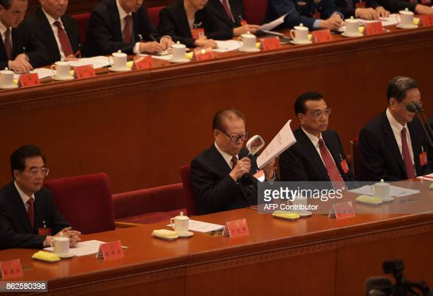 Chinese former president Jiang Zemin reads papers as Chinese President Xi Jinping delivers his address at the opening of the 19th Communist Party...