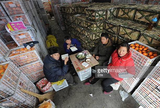 Chinese fruit sellers have a lunch break as they stock up their products ahead of the upcoming festive seasons in Hefei in eastern China's Anhui...